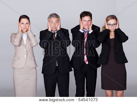 Four Businesspeople Holding Their Ears