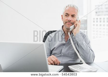 Serious mature businessman on call in front of laptop at desk in a bright office