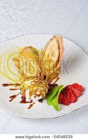 Dessert of pancake with banana, ice-cream, caramel, strawberry and mint