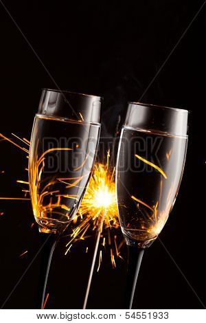 champagne glasses against christmas sparkler background