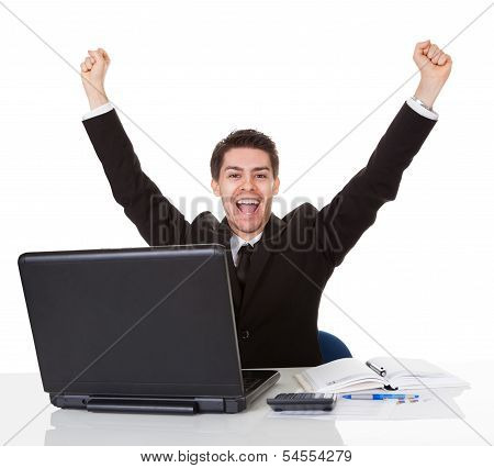 Businessman Sitting At His Desk Rejoicing