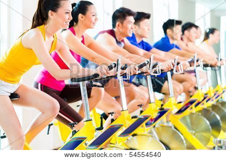 Chinese Asian sport group of men and women in fitness club or gym exercising on bikes