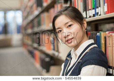Woman Sitting On Floor Next To Bookshelf