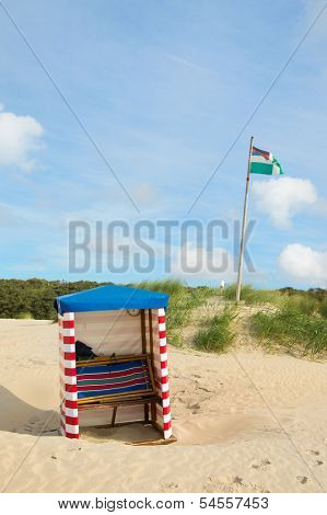Beach of German wadden island with typical striped chair and flag