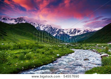 Fantastic landscape and colorful overcast sky at the foot of  Mt. Shkhara. Upper Svaneti, Georgia, Europe. Caucasus mountains. Beauty world.