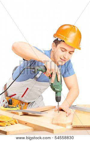 Manual worker drilling with a hand drilling machine in a workshop isolated on white background