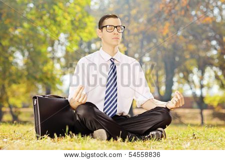 Young businessman seated on a green grass meditating in a park on a sunny day