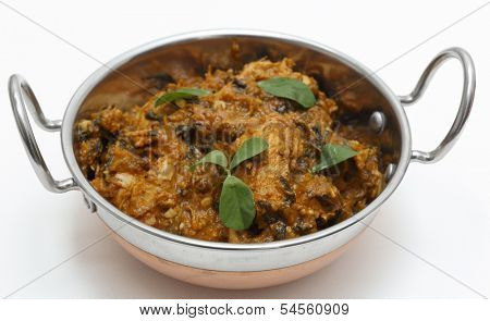 Methi murgh - chicken cooked with fresh fenugreek leaves - in a kadai, or karahi, traditional Indian wok, over white.
