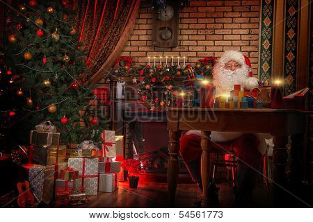 Santa Claus making Christmas gifts at home.