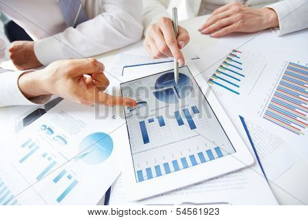 Close-up of female and male hands over business document in touchpad