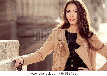 Beautiful brunette woman standing on the city street.