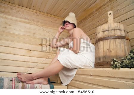 Girl In White Sheet Sits On A Bench In A Sauna
