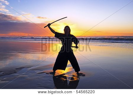Young samurai women with Japanese sword (Katana) at sunset on the beach