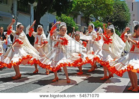 Children dancing in the street, Marbella, Spain.