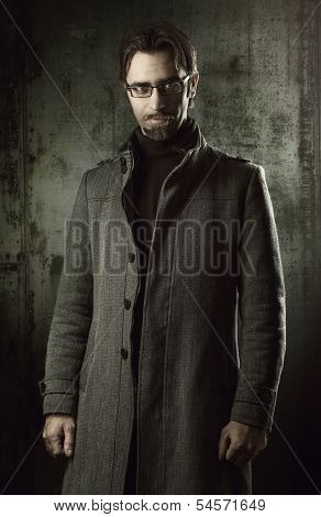 handsome man in black coat over metallic wall
