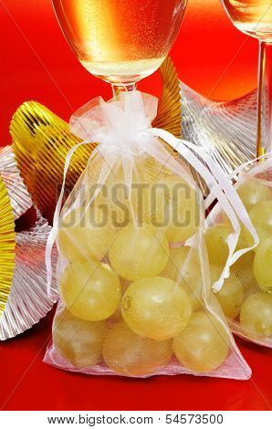some glasses with spanish champagne and sachets with the twelve grapes of luck, traditional on the New Year in Spain