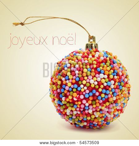 a christmas ball coated with nonpareils of different colors and the sentence joyeux noel, merry christmas written in french, on a beige background