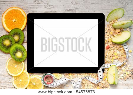 Tablet Computer With Fruit And A Measuring Tape For Weight Loss And Diets
