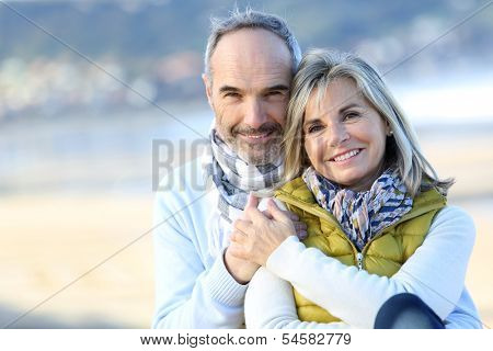 Senior couple sitting by the beach
