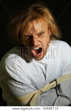 Mentally ill man in strait-jacket on black background