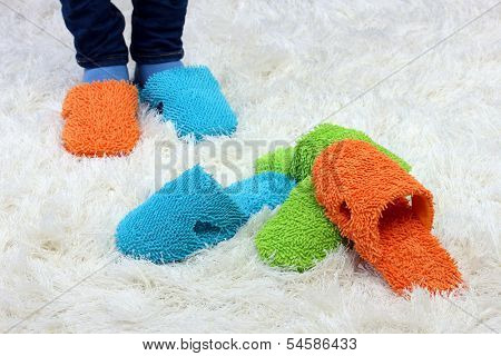 Female legs in color slippers, on carpet background