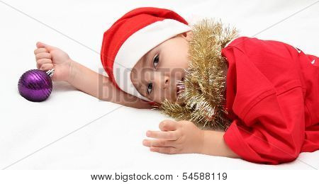 Child In Santa Claus Hat Lies On Bed