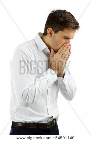 Sneezing young man isolated on white