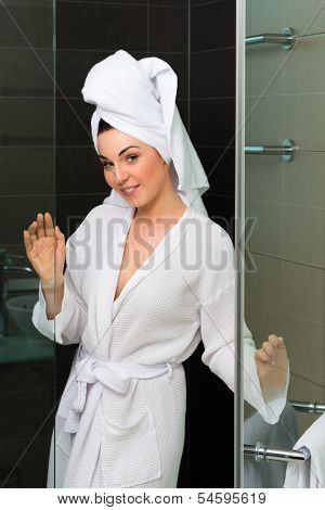 Young woman in the hotel bathroom, she comes freshly showered from the shower stall