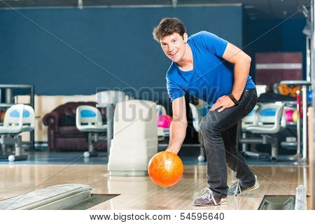 Young man in bowling alley having fun, the sporty man playing a bowling ball in front of the ten pin alley