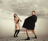 pic of exhibitionist  - laughing woman pointing at exhibitionist in the coat - JPG