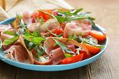 stock photo of antipasto  - salad with parma ham (jamon), tomatoes and arugula