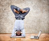 image of padmasana  - Indian businessman doing yoga headstand pose and looking at his laptop in the office at brown textured background - JPG