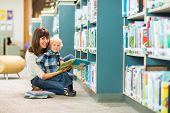 stock photo of teacher  - Portrait of happy boy and teacher reading book by bookshelf in library - JPG