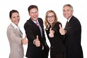 stock photo of united we stand  - Laughing group of business executives giving a thumbs up of approval and victory as they celebrate a successful outcome isolated on white - JPG