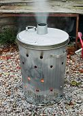 pic of dust-bin  - Garden incinerator bin burning garden waste with smoke coming out of the flue