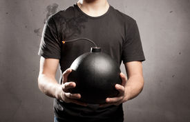 stock photo of anarchists  - young man holding an old fashioned bomb - JPG