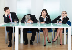 stock photo of jury  - Bored panel of professional judges or corporate interviewers lounging around on a table napping as they wait for something to happen - JPG