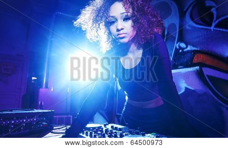 female club dj using turntable with headphones with lens flare