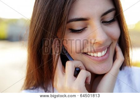 Closeup portrait of a beautiful happy woman speaking on the phone outdoors