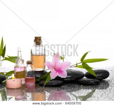 Lily flower and burn candles ,black stones, oil ,leaf on wet background