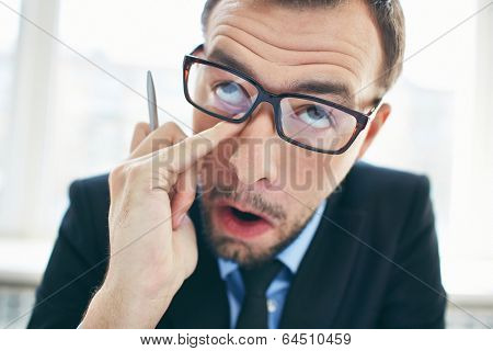Face of funny businessman in eyeglasses rubbing eye