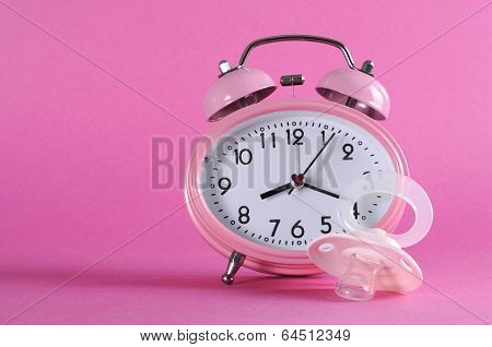 Pretty Pink Vintage Retro Style Alarm Clock With Baby Dummy Pacificer On Pink Background For Baby Gi