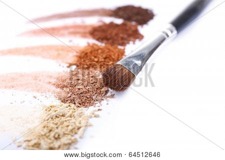 Crushed eyeshadow and professional make-up brush isolated on white