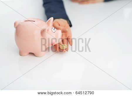 Closeup On Business Woman Feeding Piggy Bank With Coin