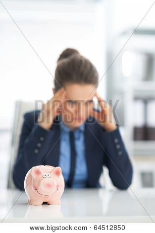 Closeup On Piggy Bank And Stressed Business Woman In Background