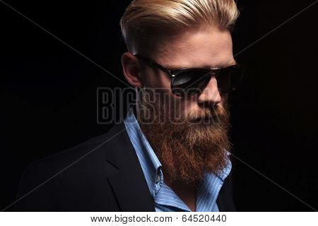 close up picture of a young bearded business man looking down, away from the camera. on a dark background