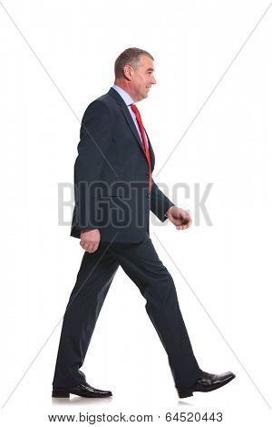 side view full length photo of a mid aged business man walking forward and looking away. isolated on a white background