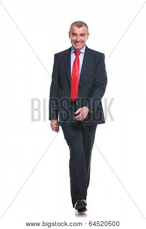 full length picture of a mid aged business man walking towards the camera and smiling. isolated on a white background