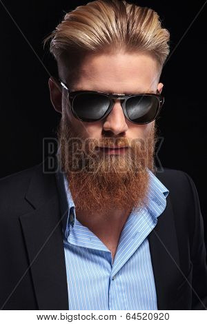 close up portrait of a young bearded business man looking into the camera. on a dark background