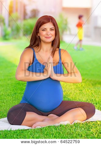 Portrait of beautiful pregnant woman with closed eyes engaged in yoga outdoors, doing exercise for healthy pregnancy, happy parenthood concept